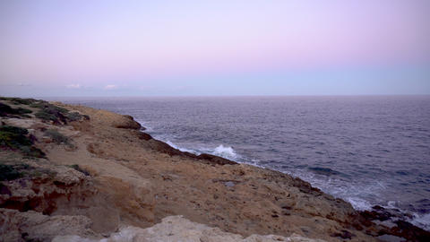 Waves on the Mediterranean Sea. Waves hit the rocks on a rocky shore. Pink Live Action