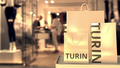 Paper shopping bags with Turin caption against blurred store entrance. Retail in Live Action