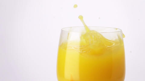 Slice of Orange Falling into a Glass of Orange Juice Live Action