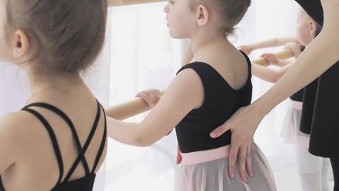 Girl dancer in ballet school learns to dance. Little Ballerina in training in Live Action