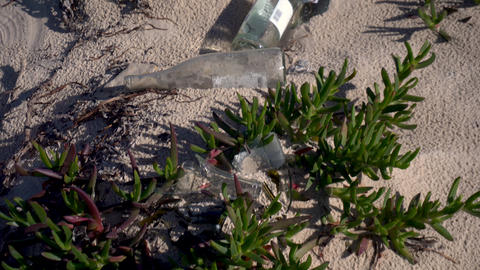 Broken glass bottles lie on the beach. Ecological pollution. Dangerous Glass Live Action