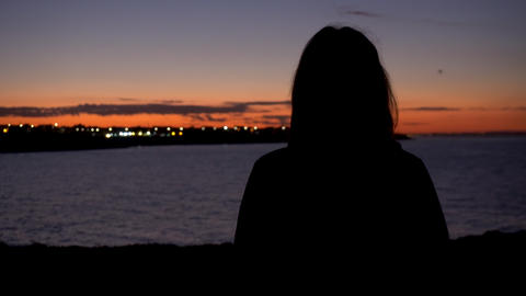 A young woman is watching the sunset. A woman stands on a cliff in front of the Live Action