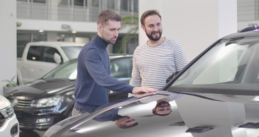 Portrait of two Caucasian man standing in car dealership and looking at car Live Action