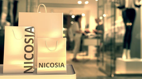 Paper shopping bags with Nicosia caption against blurred store entrance. Retail Live Action