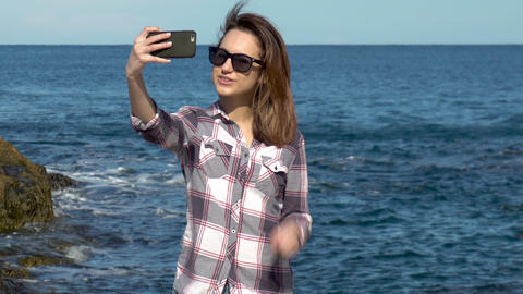 Young woman makes selfie on a smartphone on a background of the sea. Woman takes Live Action
