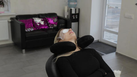 Beautiful woman lies on a procedure in a beauty salon with cotton pads on her Live Action