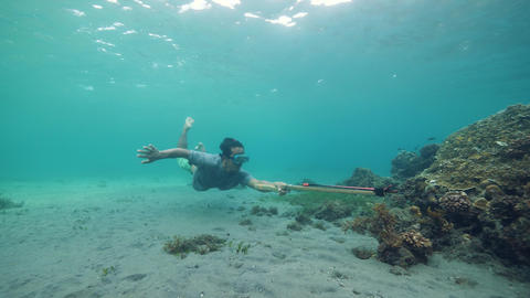 Underwater scene, a fish hunter try to catch a fish using wooden speargun Live Action