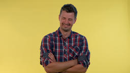Happy young man bursting in laughter on yellow background. He is in checkered Live Action