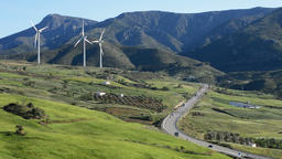 Wind turbines energy moving at field together a road and mountains at sunny day Footage