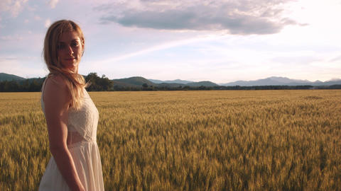 Young woman standing in the wheat field watching sunset looks into the camera Footage