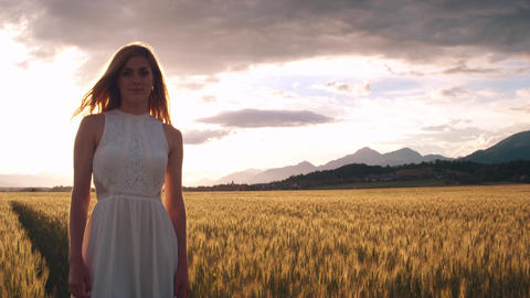 Jib shot - Young woman standing in the wheat field and looking into the camera Footage