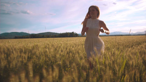 Slow motion - In front of a girl in a white dress running through field of wheat Footage