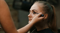 Make up artist doing professional make up of young woman Footage