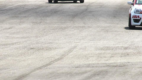 Passing by cars on track tarmac leaving traces and rubber Footage