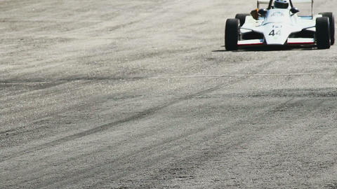 Formula 1 car passes by hot racing track tarmac Footage