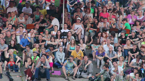 Audience watching the show, people sit on concrete Footage