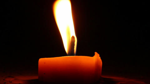 Burning candle in the night. Wind blows and flame shimmers Footage
