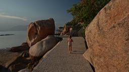 Little Girl Runs along Rocky Path on Beach against Azure Sea Footage