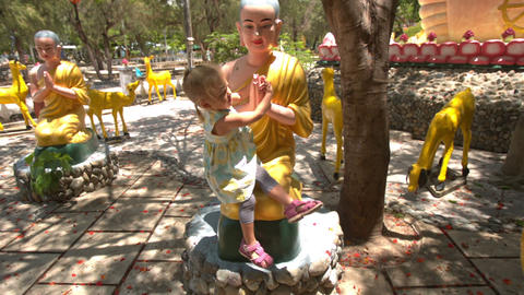Little Girl Sits on Buddha Statue Plays in Temple Park Footage