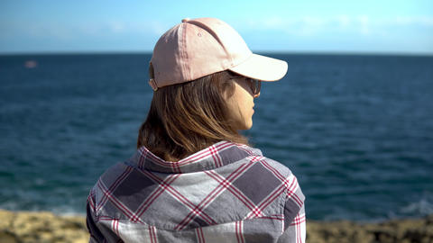 A young woman is looking at the sea. The girl in the cap admires nature. Woman Live Action