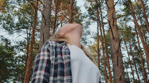 Young girl looking to sky in pine forest. Romantic girl turning and looking up Live Action