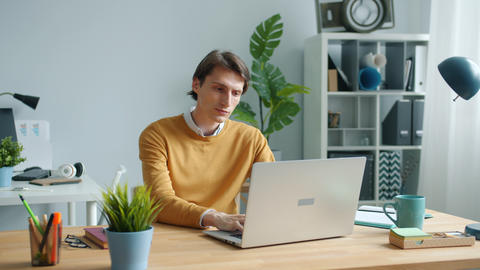 Exhausted guy using laptop typing then touching head feeling tired at work Live Action