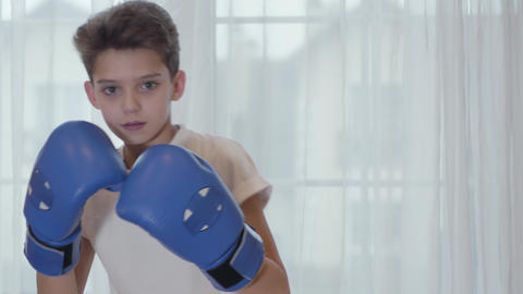 Brunette Caucasian boy showing his boxing skills at camera. Cute schoolboy in Live Action