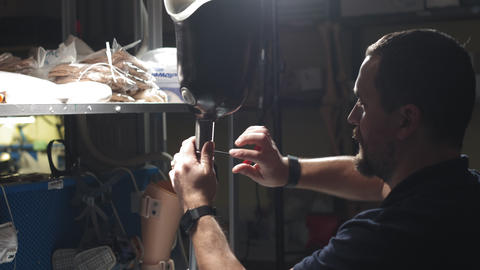 Production of a prosthetic leg. A man creates part of the... Stock Video Footage