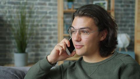 Joyful student talking on mobile phone in apartment enjoying conversation Live Action
