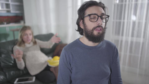 Exhausted Caucasian man in eyeglasses making faces as his pregnant wife yelling Live Action