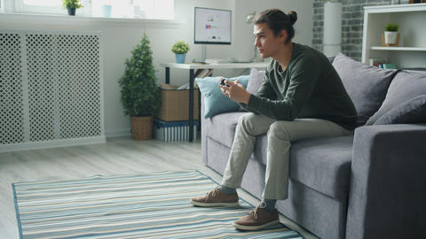 Handsome student playing video game in apartment having fun with gadget Live Action
