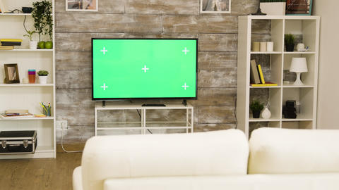 Big green screen TV in a bright and well lit living room with nobody in it Live Action