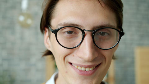 Slow motion portrait of attractive guy wearing glasses smiling in house alone Live Action