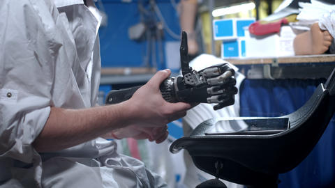 A scientist engineer is testing an electronic bionic prosthetic arm. He moves Live Action