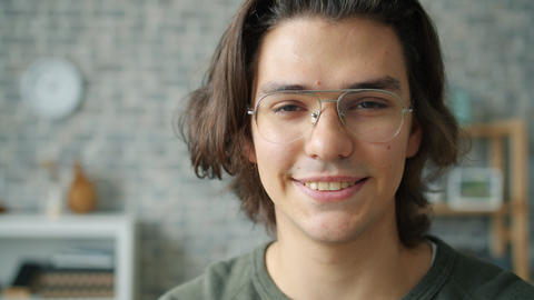 Slow motion of attractive guy in glasses serious then smiling in apartment Live Action