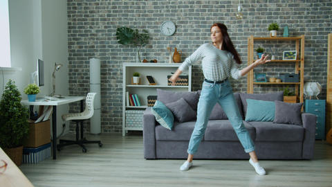 Good-looking girl in casual clothing dancing alone in apartment having fun Live Action