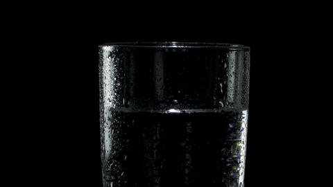 A wet glass of water spins in the dark with slow approach Live Action