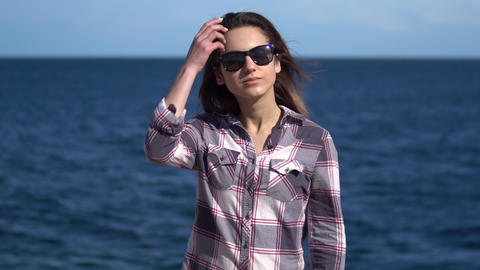 A young woman on a background of the sea. Girl in sunglasses in sunny weather Live Action
