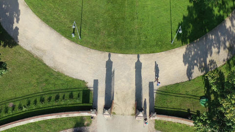 Old historical manor mansion gates and tourists shadows in park, aerial view Live Action