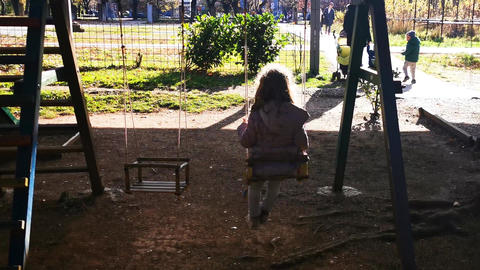 Litlle girl swinging in the park Live Action