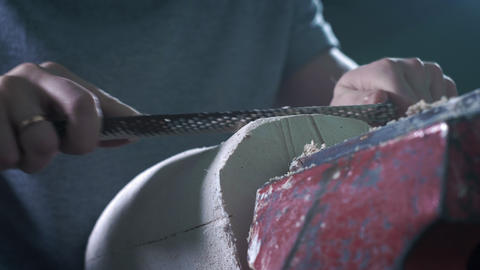 Production of a prosthetic leg. A person processes a plaster cast of a part of Live Action