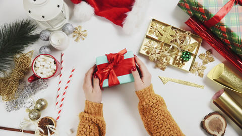 Woman wrapping christmas present and decorating is by wooden star Live Action