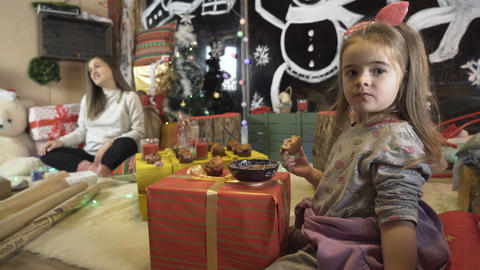 Little blonde girl eating Christmas meals while her pregnant mom talks with Live Action