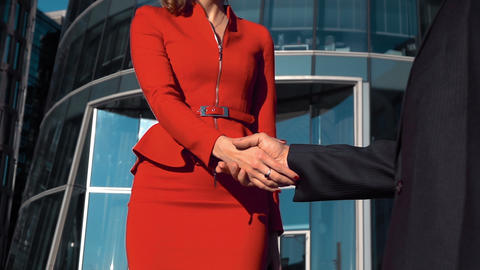 Successful businesswoman and businessman shaking hands outdoor Live Action