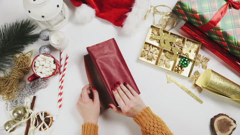 Woman preparing red paper to wrapping Christmas Presents Live Action