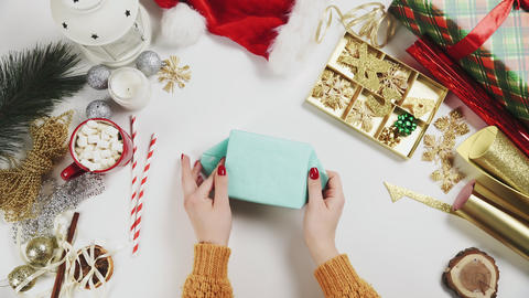 Woman wrapping christmas present, gift on white table background with holiday Live Action