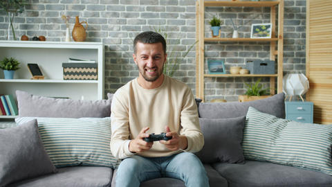 Portrait of cheerful carefree guy playing computer game in house alone Live Action