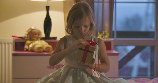 Caucasian girl closing casket with red bow and hugging her gift. Door closing at Live Action