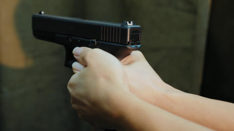 Female hands holding pistol ready shoots to target, close-up Live Action