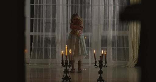 Weird Caucasian girl standing in candlelight with doll. Frightening child Live Action